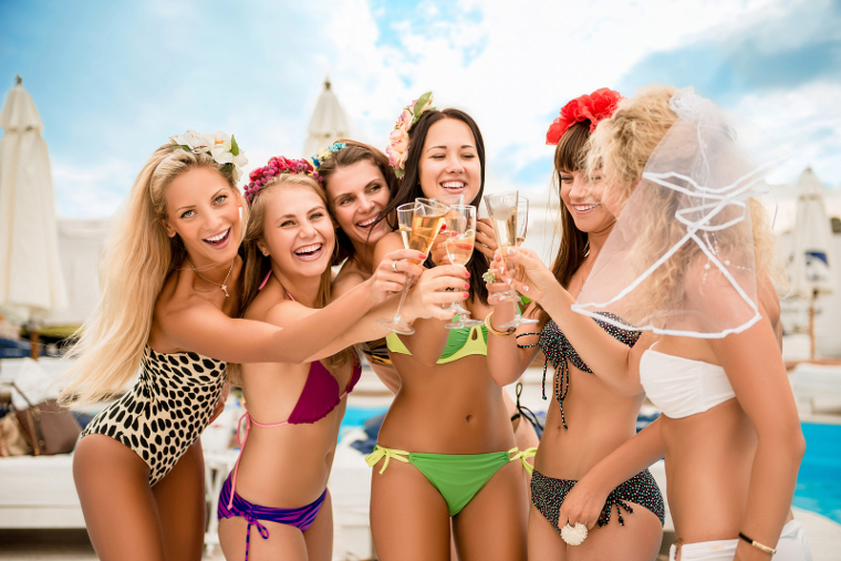 Happy sexy girl clinking glasses at bride's hen party by the pool