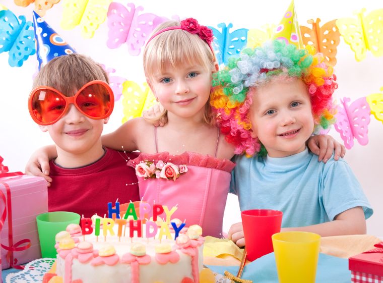 Three kids are happily posing during birthday party